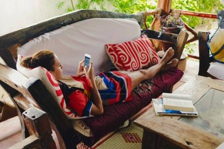 Young woman lying on sofa in porch communicates social networks