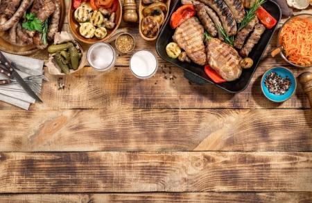 barbecued steak, sausages, beer and grilled vegetables on wooden