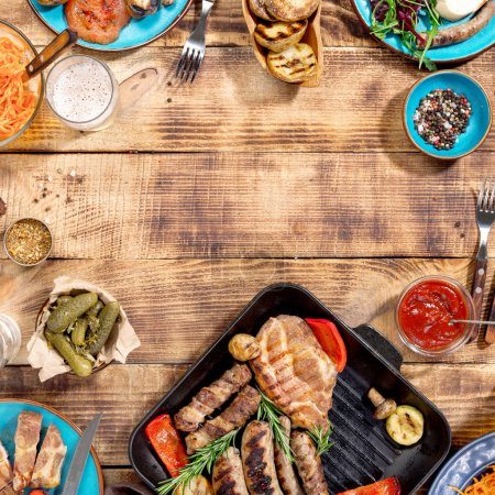 Barbecued steak, sausages and grilled vegetables on wooden picni