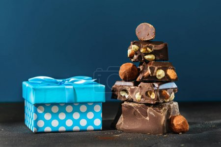 Dark chocolate stack and gift box on blue background