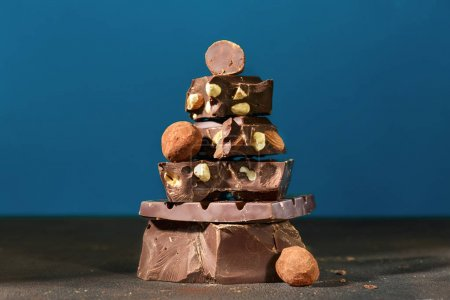 Photo for Dark chocolate stack and truffle chocolates on blue background - Royalty Free Image