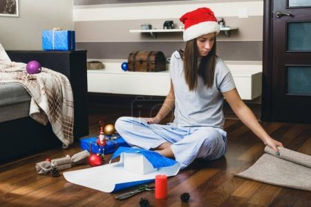 Young woman in santa claus hat wraps Christmas gifts while sitting on the floor at home