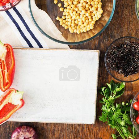 Black quinoa, chickpeas, peppers, cucumber, tomatoes and parsley on rustic wooden table, top view. Ingredients for cooking a healthy vegetarian salad