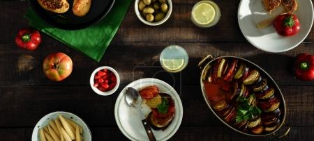 Different vegetarian food on wooden table. Ratatouille, chickpeas cutlets, lemonade and various snacks, top view.
