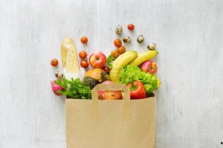 Photo pour Sac en papier vue de dessus de différents aliments frais de santé sur fond en bois blanc. Vue de dessus. Poser de plat - image libre de droit