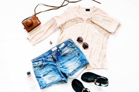 Summer set of female clothes on white background. Female denim shorts with blouse and sandals, top view, flat lay