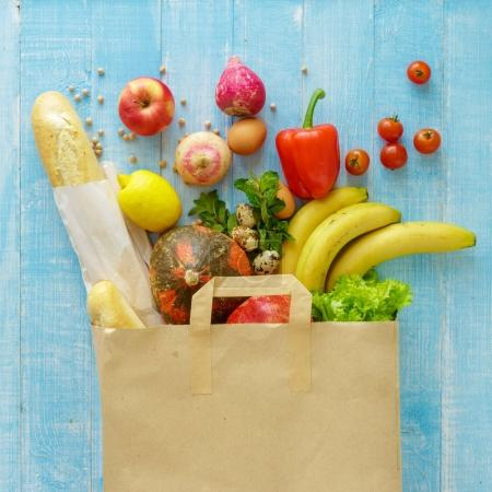 Paper bag of different health food on blue wooden background