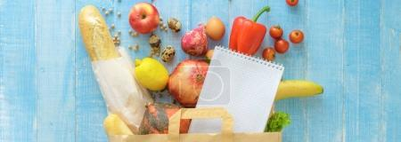 Paper bag different fresh health food notebook on wooden backgro