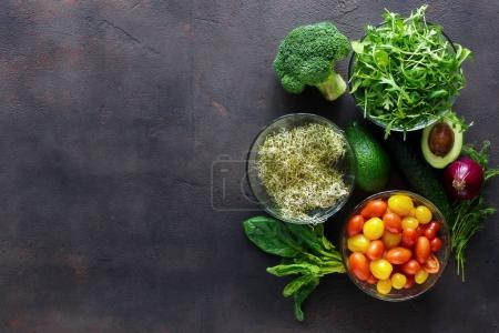 Photo for Set of ingredients for detox salad. Broccoli, spinach, avocado, arugula, pea shoots, alfalfa, onion, cherry tomatoes and cucumber on grey, top view - Royalty Free Image