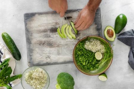Photo for Top view man cooking a detox salad on a white surface, rustic style - Royalty Free Image
