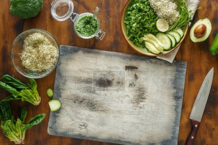 Photo for Top view cutting board with ingredients for cooking detox salad on a dark wooden background - Royalty Free Image