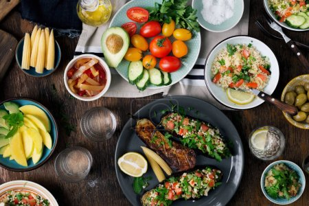 Vegetarian table with different food. Stuffed eggplant and porridge bulgur with vegetables, top view