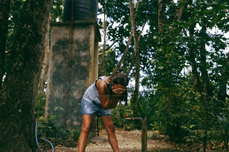 Woman traveler washing hands in dense tropical for...