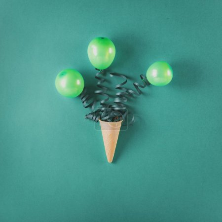 Ice cream cone with balloons and streamer. Minimal birthday concept