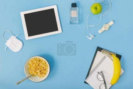 Feminine office workspace concept, white tablet and notebook with corn flakes in bowl and clipboard with headphones on blue table