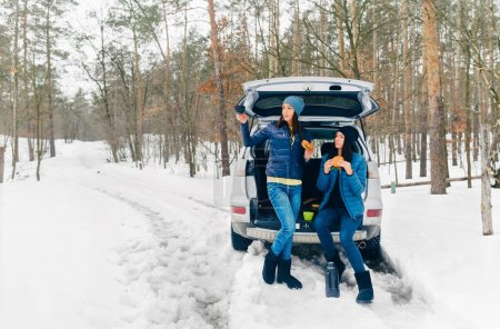 Two young women sitting in car trunk in winter forest