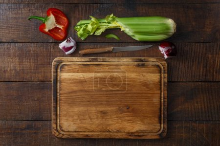 Wooden kitchen board with fresh vegetables on dark wooden table