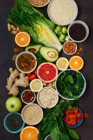 Photo for Top view set clean eating. Vegetarian healthy food - different vegetables and fruits, superfood, seeds, cereal, leaf vegetable on dark background. Flat lay - Royalty Free Image