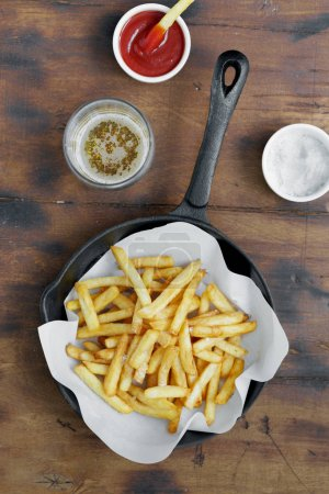 French fries served in frying pan on wooden table with ketchup and beer, top view