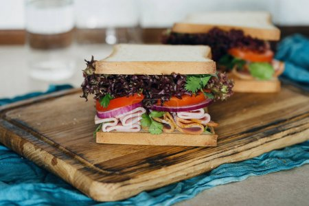 Photo for Large sandwiches with turkey meat served on a chopping board close up - Royalty Free Image