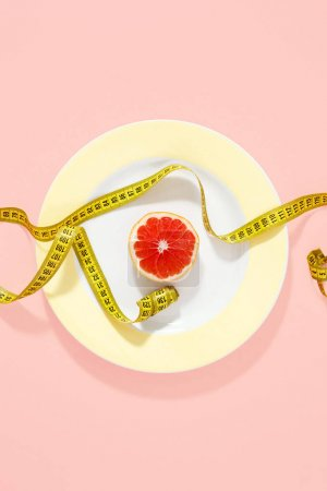 Yellow plate with measuring tape and half grapefruit on pink background. Top view, flat lay. Diet minimal concept