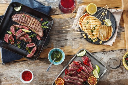 Beef steak grill and chicken steak grill on wooden table with sauces and red wine on sunny day. Outdoors Food Concept