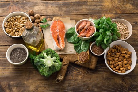 Photo for Health food fitness. Food sources of omega 3 and omega 6 on dark background top view. Foods high in fatty acids including vegetables, seafood, nut and seeds - Royalty Free Image