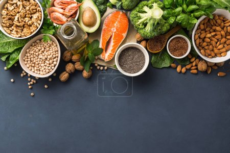 Photo for Food sources of omega 3 on dark background with copy space top view. Foods high in fatty acids including vegetables, seafood, nut and seeds. Health food fitness - Royalty Free Image