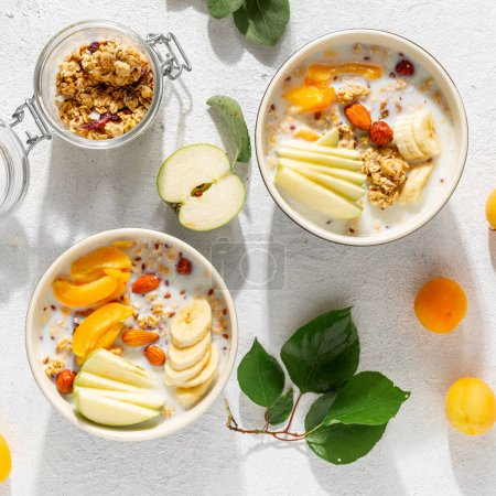 Photo for Granola fruit with milk peanut butter in bowl. Healthy breakfast cereals top view - Royalty Free Image