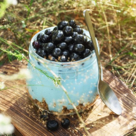 Photo for Glass jar of healthy yogurt with fresh berries blueberries and oats served in a glass jar outdoors. Healthy fresh natural breakfast concept - Royalty Free Image