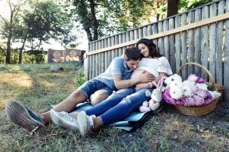 Man and pregnant woman near wooden fence