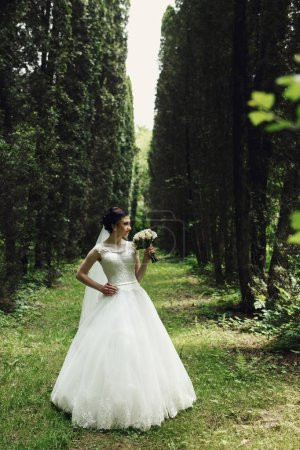Brunette bride poses in the forest