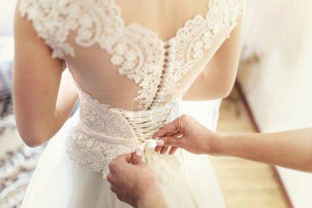 Photo pour Femme avec manucure blanche ajuste les lacets blancs sur le corset de la mariée - image libre de droit