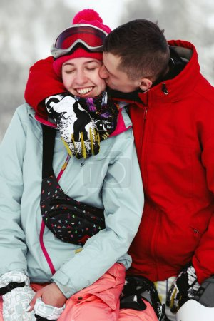 Couple on the snowboards in mountains