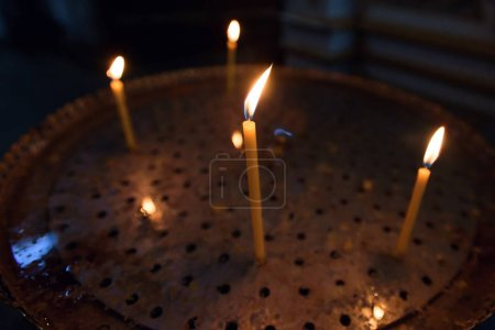 Yellow candles burn in church