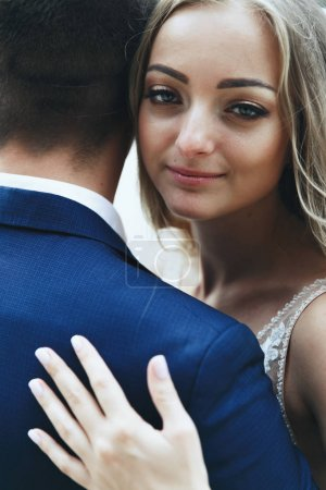 Portrait of beautiful bride leaning to groom's shoulder tender