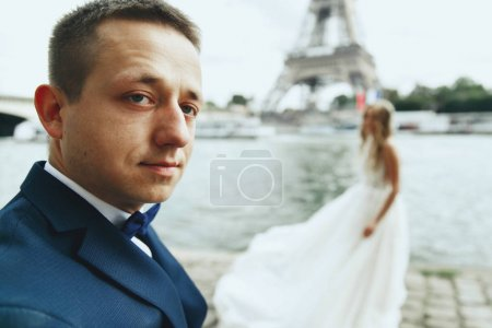 Luxury wedding couple poses before river Seine and the Eiffel Tower somewhere in Paris
