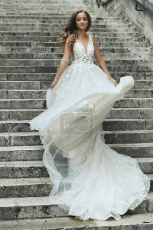 Blonde bride in luxury wedding dress whirls on footsteps somewhere in Paris