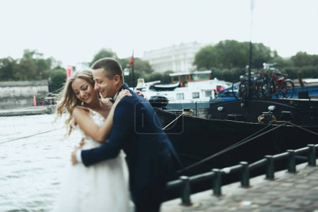 Classy groom and bride in luxurious dress pose before the river Seine somewhere in Paris