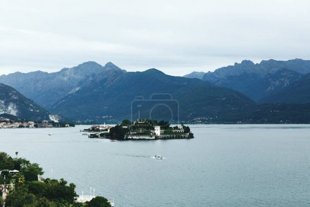 Look over the roofs of southern city at beautiful mountains and lake before them