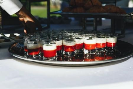 Little shots with alcohol stand on a silver tray