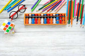 Colorful back to school supplies top border over white table. Mental arithmetic. Space for text.