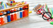 Colorful back to school supplies double border over white table. Mental arithmetic scores abacus. Space for text.