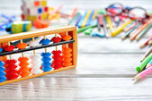Close up view of abacus scores mental arithmetic with colorful back to school supplies over white table. Space for text.