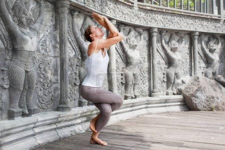 Photo pour Jeune femme faisant du yoga dans un temple abandonné sur une plateforme en bois. Pratique en Thaïlande - image libre de droit