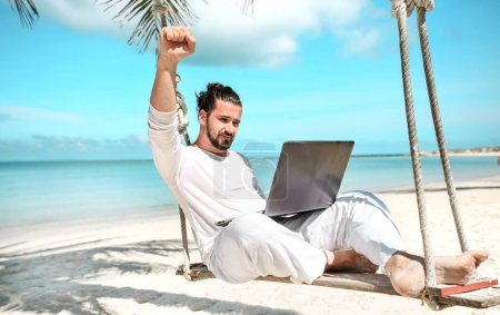 Photo for Businessman freelance on beach swing with laptop - Royalty Free Image