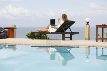 Photo for Work At Beach. Successful Business Woman Working Online In Internet Using Laptop Computer Outdoors. Girl Typing On Keyboard While Relaxing By Sea In Summer. Communication Technology Concept - Royalty Free Image