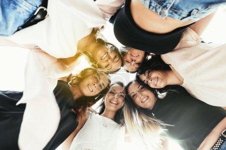 Women friends standing in circle.