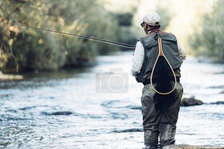 Fly fisherman using flyfishing rod.