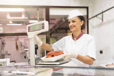 Photo pour Jolie femme de boucherie qui travaille dans une boucherie . - image libre de droit